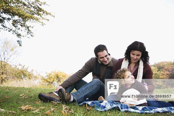 Paar und ihre Tochter zusammensitzen und lächelnd