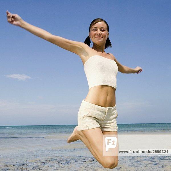 Nahaufnahme einer jungen Frau springen am Strand