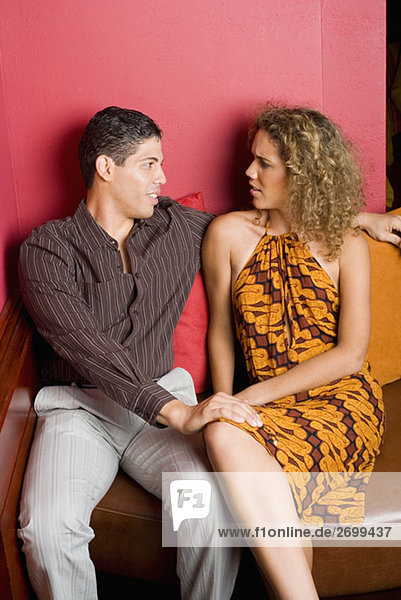 Teenage girl and a young man sitting on a couch
