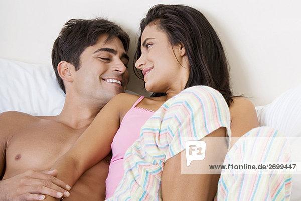 Erhöhte Ansicht eines jungen Paares auf dem Bett liegend