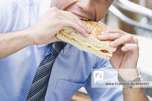Nahaufnahme eines Kaufmanns Essen einen Käse-sandwich