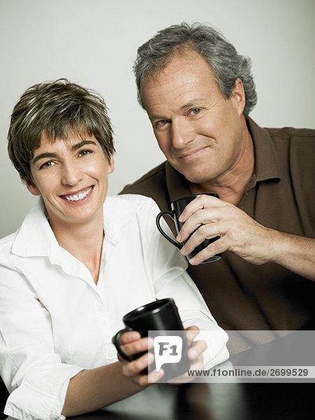 Porträt eines ausgereiften Paares hält Tassen Tee und lächelnd