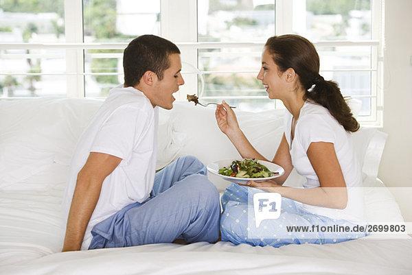 Seitenansicht einer jungen Frau Fütterung junger Mann Salat