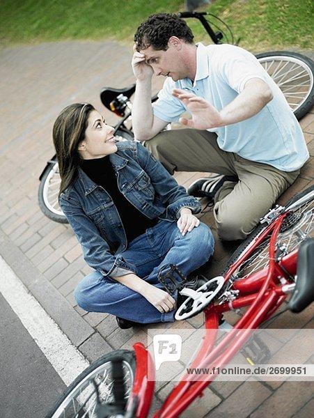 Erhöhte Ansicht eines Mitte adult Paares sitzen mit Fahrrädern und Blick auf einander