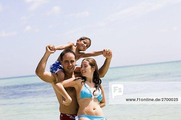 Mitte Erwachsenen Mann mit seinem Sohn auf seinen Schultern mit einer jungen Frau Stand vor ihm am Strand