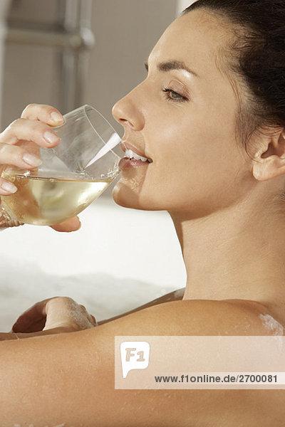 Seitenansicht einer jungen Frau trinken Weißwein in der Badewanne