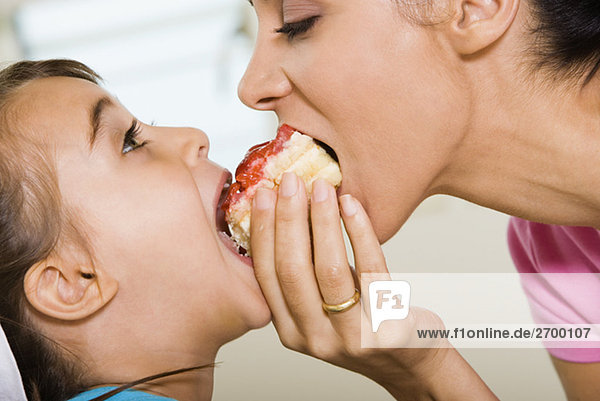Close-up of mother sharing a pastry with her daughter