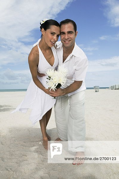 Porträt eines jungen Paares Tanz am Strand und Blumen halten