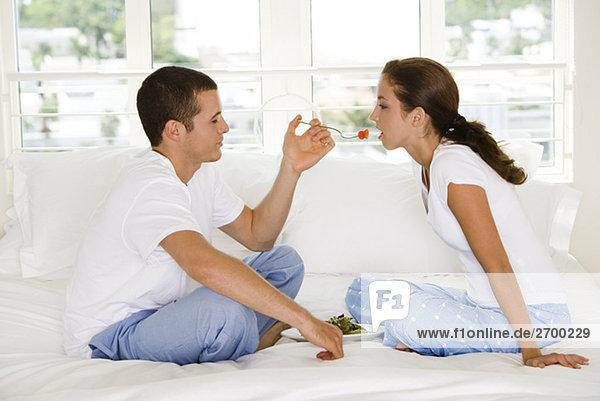 Seitenansicht eines jungen Mannes Fütterung einer jungen Frau Kirschen