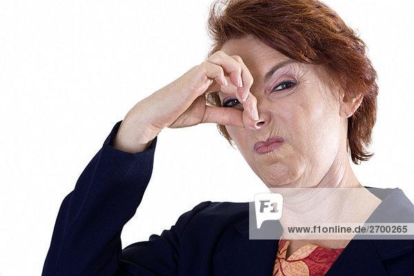 Porträt von geschäftsfrau hält Nase