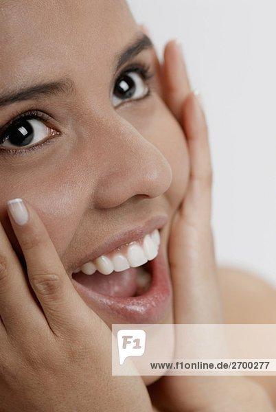 Nahaufnahme einer jungen Frau mit den Händen auf dem Kopf lachen
