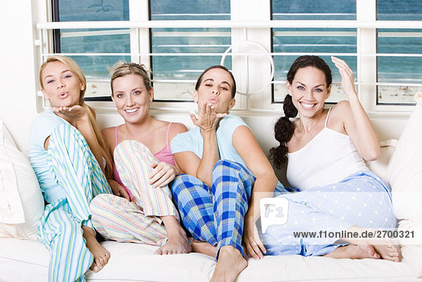 Portrait of four young women sitting on a couch blowing kisses