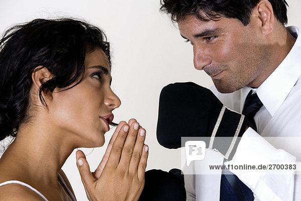 Seitenansicht einer jungen Frau vor ein Mitte Erwachsenen Mann mit Boxhandschuhen Schriftsatz