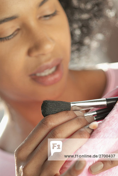 Nahaufnahme einer jungen Frau die Make-up Pinsel aus ihrem Geldbeutel