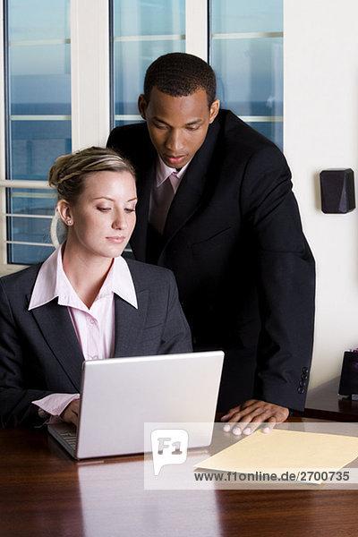 Nahaufnahme eines Kaufmanns und einer geschäftsfrau  Blick auf einem laptop