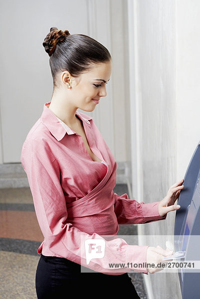 Side profile of a businesswoman inserting a credit card into an ATM