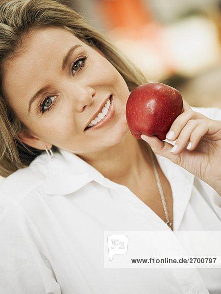 Portrait einer Mitte erwachsen frau hält einen Apfel und lächelnd