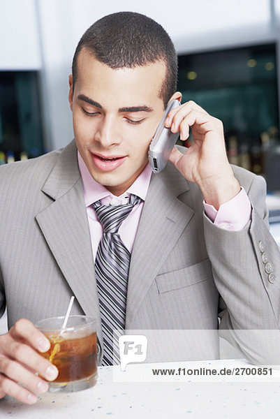 Close-up of a businessman holding a cocktail and talking on a mobile phone in a bar
