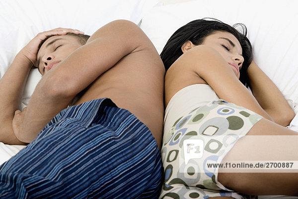 Seitenansicht eines jungen Paares auf einem Bett liegend