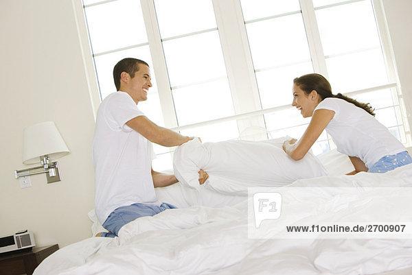 Seitenansicht eines jungen Paares haben eine Kissenschlacht