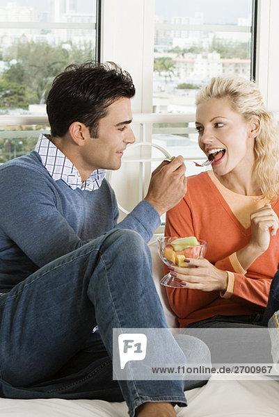 Nahaufnahme eines jungen Mannes Fütterung Salat mit einer jungen Frau