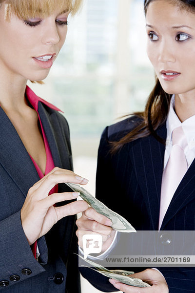 Close-up of a businesswoman giving a dollar bill to another businesswoman
