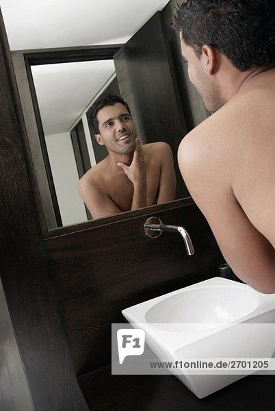 Nahaufnahme eines jungen Mannes suchen in einen Spiegel und lächelnd