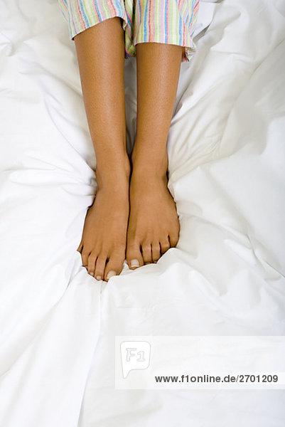 Niedrige Schnittansicht einer Frau auf dem Bett
