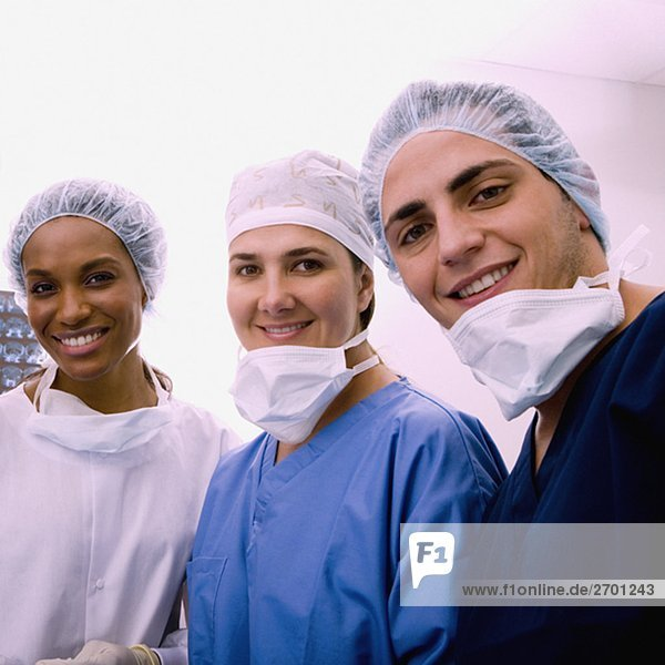 Portrait of a male surgeon and two female surgeons smiling