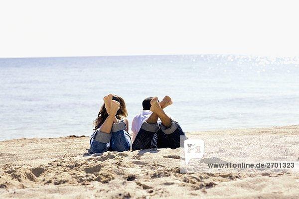 Rückansicht eines Mitte Erwachsenen Mann und eine junge Frau liegen am Strand