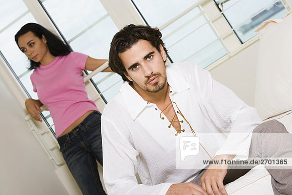 Portrait of a young man sitting on the bed with a young woman standing behind him