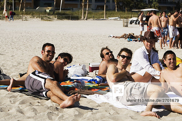 Young men and two young women sunbathing on the beach  South Beach  Miami  Florida  USA