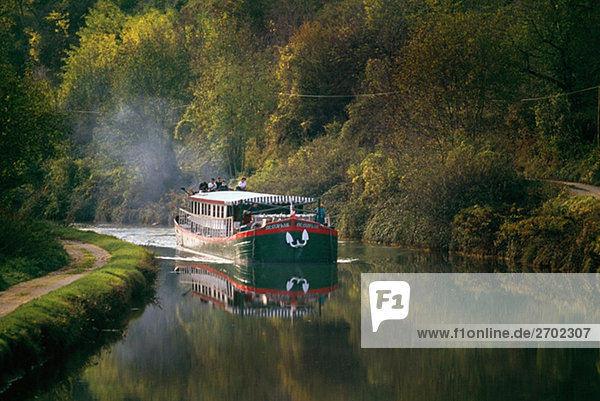 Side view of a luxury barge moving upstream  France