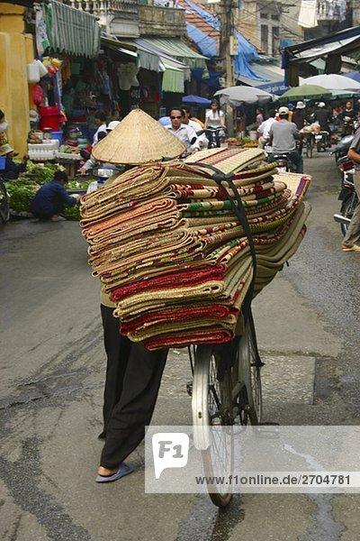 Rückansicht eines Mannes verkaufen Teppiche in einem Markt  Hanoi  Vietnam