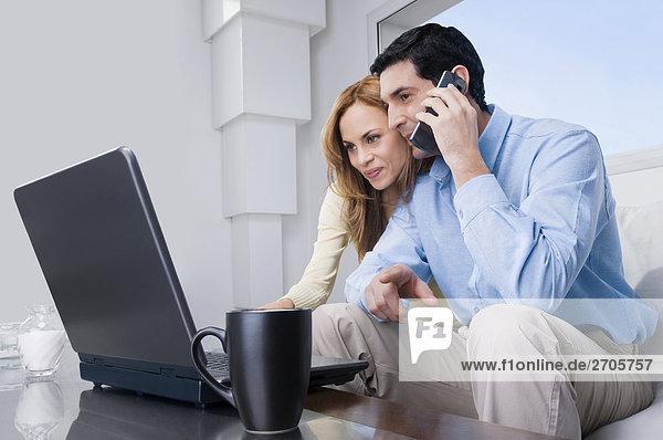 Mitte Erwachsenen Mann sprechen auf einem Mobiltelefon und einer Mitte erwachsen frau arbeiten auf einem laptop