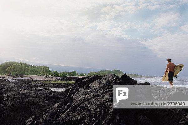 Mann zu Fuß mit einem Surfbrett auf den Felsen  Hawaii  USA