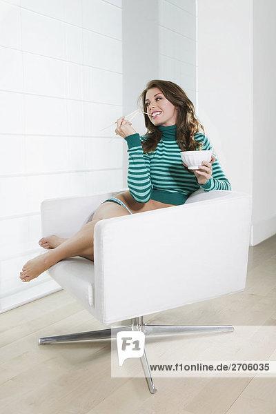 Junge Frau im Sessel sitzen und Essen