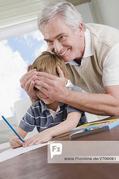 Senior man covering eyes of his grandson and smiling