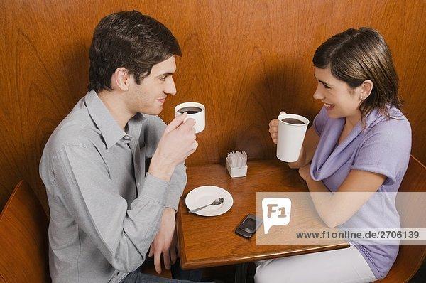 Erhöhte Ansicht eines jungen Paares mit Kaffee in einem Café