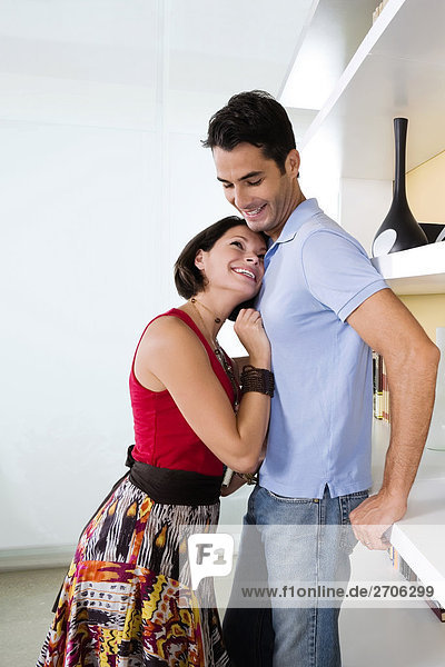 Side profile of a young woman embracing a mid adult man and smiling
