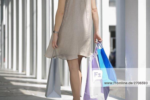 Mitte Schnittansicht einer jungen Frau tragen Tragetaschen
