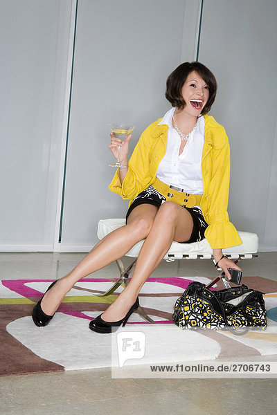 Junge Frau mit einem Glas Martini und lachen