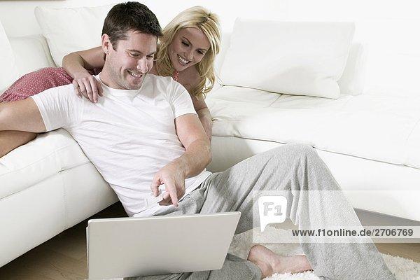 Nahaufnahme eines Mitte Erwachsenen Mannes mit seiner Frau lächelnd und Blick auf einen laptop