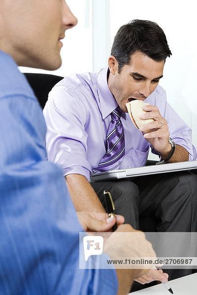 Junger Mann mit einem Erwachsenen Mann Mitte sitzend und Sandwich zu essen