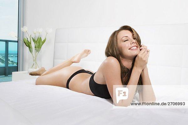 Junge Frau auf dem Bett liegend und lächelnd