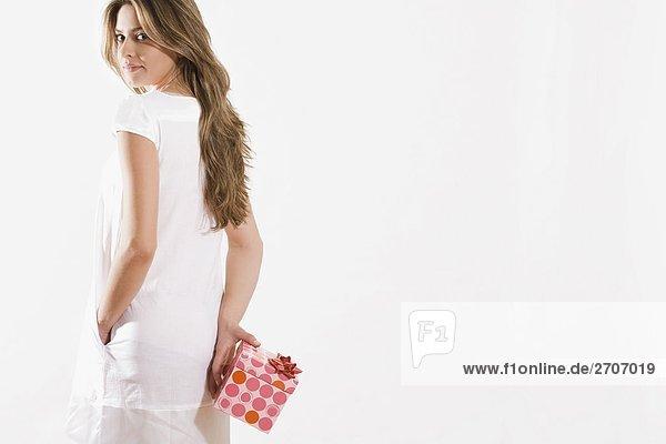 Portrait of a junge Frau hält ein Geschenk