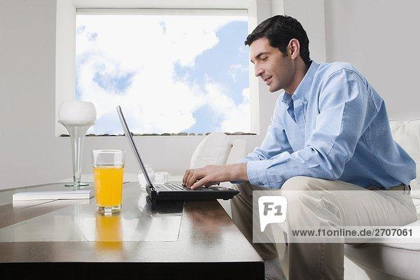 Mitte Erwachsenen Mann arbeitet auf einem Laptop mit einem Glas Saft auf dem Tisch