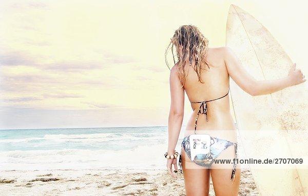 stehend junge Frau junge Frauen Strand Surfboard Rückansicht Ansicht
