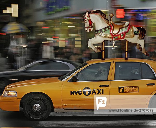 Carousel horse on a yellow taxi  New York City  New York State  USA