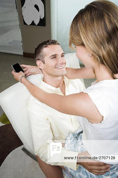 Junge Frau sitzt auf dem Schoß eines jungen Mannes lächelnd